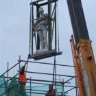 Off his perch . . . The statue of Trooper David Mickle Jack is lowered from the top of the Boer...