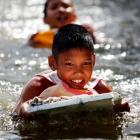 Boys play in the water in a flooded slum as floods advance into central Bangkok yesterday. The...