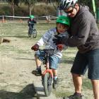 Brett Jarvie, of Wanaka, helps son Joshua (5) over the obstacles at the Meridian Bike Jam in...