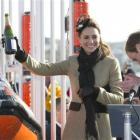 Britain's Prince William applauds, as Kate Middleton holds uo a champagne bottle after naming a...