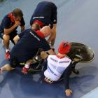 British cyclist Philip Hindes sits on the ground after crashing during the men's team sprint...