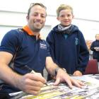 Caleb Dickson (9) watches Klark Quinn sign posters at Goldfields Primary School. Photo by Sarah...