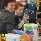 Cameron Gillies (6) visits Mosgiel New World to learn from operator Debbie Wilson how to use the...