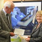 Campaign committee chairman Dr Brian McMahon hands over the latest donation to National Bank...
