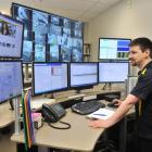 Campus Watch control room operator Gavin Osborne looks over one of the monitors in the renovated...
