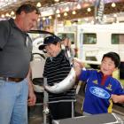 Canterbury Sports Fishing Club's Ray Eade watches as James (10) and Jacob Yee (5) hold a live...