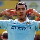 Carlos Tevez of Manchester City celebrates, gesturing towards Norwich City fans, after scoring...