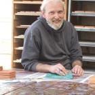 Ceramicist Vaughan Tessier-Varlet creates designs on tiles at the Lazy Cat Pottery and Tileworks...