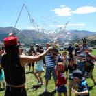 Children grasp at bubbles created  by entertainer Rob FireNix, of Nelson. Photos by Guy Williams.
