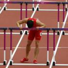 China's Liu Xiang kisses the last hurdle in his lane after crashing into the first hurdle and...