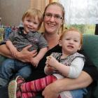 Chrystal O'Malley holds twins Chase, left, and Amelia Gillespie (13 months), at home in...