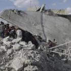 Civil defence members and civilians search for survivors under the rubble of a site hit by what...