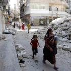 Civilians walk near a destroyed building after a Syrian Air Force fighter jet launched a bomb in...