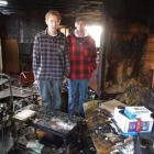 Colin Melvin (left) and a friend, Sid Winterburn, stand in the gutted lounge of Mr Melvin's...