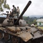 Congolese children play on a destroyed military tank, abandoned by the M23 rebel fighters near...