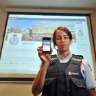 Constable Kristyn Adamson displays a smartphone and large screengrab of Dunedin police's new...