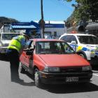Constable Ryan Fitzgerald breath-tests drivers in Queenstown yesterday. Photo by Olivia Caldwell.