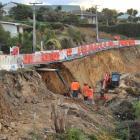 Contractors inspect a slip under Portobello Rd, at Turnbulls Bay, last night. Photos by Linda...