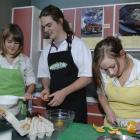 Casey Broad, Declan Smith and Gina Manning bake a cake in the Logan Park High School food...