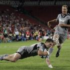 Cory Jane scores a try for the Hurricanes against the Lions watched by teammate James Broadhurst...