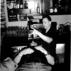 Craft Bar duty manager Michael Campbell pours liqueur from a  bottle into the mouth of a patron,...