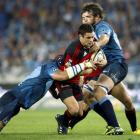Crusaders first-five Daniel Carter, center, is tackled by Bulls captain Victor Matfield, left,...