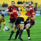 Crusaders forward Kieran Read spills the ball as he is hit by Hurricanes winger Hosea Gear....