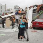 CTV staff comfort each other as rescue personnel work to rescue people trapped in the collapsed...