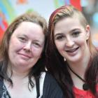 Cyndi Philip (29) and Zydina Barringer (19) laugh after being shorn for a good cause yesterday at...