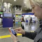 """Daisuke Tsuda tweets with his mobile phone at a station in Tokyo. """"Japan is enjoying the richest..."""
