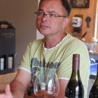 Dan Asher and his savoury pinot noir from Swallows Crossing vineyard, which slopes  steeply down...