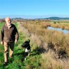 Dan Lyders (75) walks his dog Bill Bungard along the flood bank on the true left side of the...