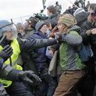Danish riot police push back protestors, one bleeding, at right, during a demonstration outside...