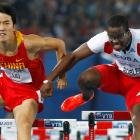 Dayron Robles of Cuba (R) makes contact with Liu Xiang of China as they go over the final hurdle...