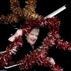 DCC events manager Marilyn Anderson examines a tattered tinsel Rudolph decoration which will not...