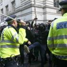 Demonstrators are confronted by police officers as they participate in a protest against student...