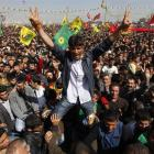 Demonstrators gesture and hold Kurdish flags during a gathering in the southeastern Turkish city...