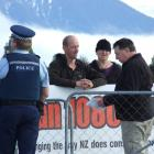 Department of Conservation principal compliance officer Alan Christie (right) issues professional...