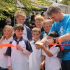Deputy Prime Minister Bill English, helped by Lumsden School pupils, cuts the ribbon to open...