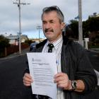 Detective Sergeant Brett Roberts, of Dunedin CIB, with a letter calling for information about...