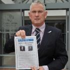 Detective Sergeant Derek Shaw with a copy of a reward poster offering $20,000 for information on...