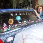 Donna Demente with the art car she is redecorating. Photo by Sally Rae.