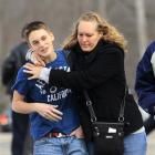 Doug Gasper, a ninth grader at Chardon High School, is hugged by his mother, Sandy, as they leave...