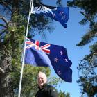 Doug MacKenzie with his preferred flag option and the present New Zealand flag outside his...