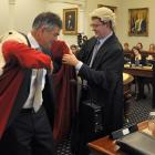 Dunedin City Council chief executive Paul Orders helps Mayor Dave Cull into his robes. Photo by...