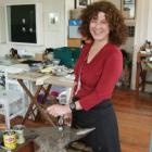 Dunedin jeweller Lynn Kelly stands beside an anvil in Lure Gallery. Photo supplied.