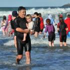 Dunedin Mayor Dave Cull, with granddaughter Carli Hutchinson (2), exit the water at St Clair...