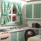 Dunedin Miniaturist Club member Jill York looks through the window of the miniature kitchen she...