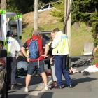Dunedin police interview a bystander as St John Ambulance staff treat a cyclist (obscured) who...