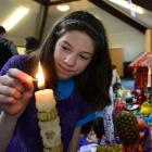 Dunedin pupil Sofia Barriga (12) lights a candle to celebrate the dead in Dunedin on Saturday....